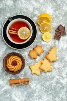 Vista de cima uma xícara de chá rodelas de limão, paus de canela, biscoitos, chocolate, superfície cinza