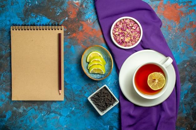 Vista de cima uma xícara de chá tigelas com pétalas de flores secas e fatias de chá de lápis de toalha de mesa roxo limão no caderno na superfície vermelha azul