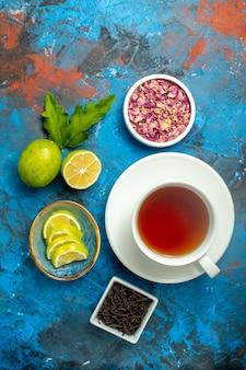Vista de cima uma xícara de chá tigelas com pétalas de flores secas e rodelas de chá de limão na superfície azul vermelha