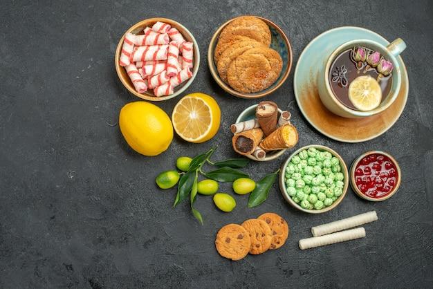 Vista de cima uma xícara de chá uma xícara de chá de ervas, frutas cítricas, doces, biscoitos, geleia