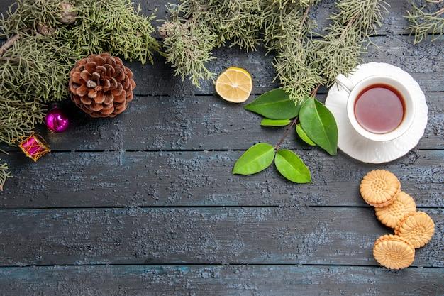 Vista de cima, uma xícara de cone de chá do abeto deixa brinquedos de natal, fatia de limão e biscoitos na mesa de madeira escura