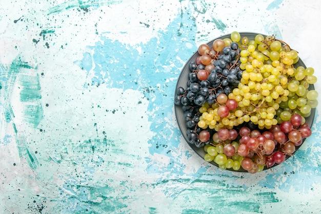 Vista de cima uvas frescas coloridas frutas suculentas e maduras em fundo azul frutas baga suco fresco maduro vinho