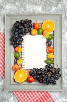 Vista de cima uvas frescas escuras com laranjas e feijoa dentro da moldura na superfície branca frutas maduras frescas
