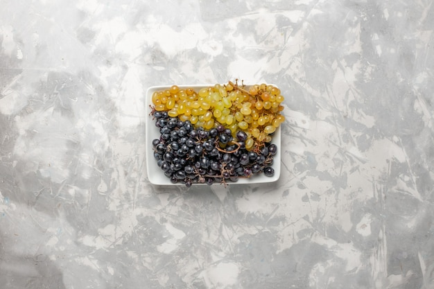 Vista de cima uvas frescas frutas maduras e suculentas dentro do prato na superfície branca fruta vinho fresco árvore de suco de uva