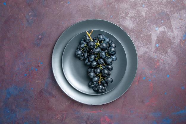 Vista de cima uvas frescas maduras frutas escuras dentro da placa na superfície escura vinho uva fresca planta árvore de frutas maduras