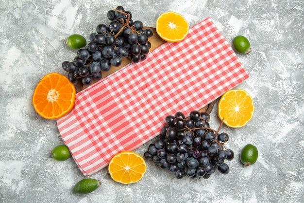 Vista de cima uvas pretas frescas com feijoa e laranjas no fundo branco frutas maduras frescas maduras
