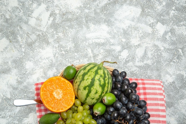 Vista de cima uvas pretas frescas com laranja e feijoa na superfície branca clara com frutas maduras frescas