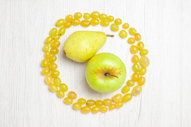 Vista de cima uvas verdes frescas com pêra e maçã na mesa branca.