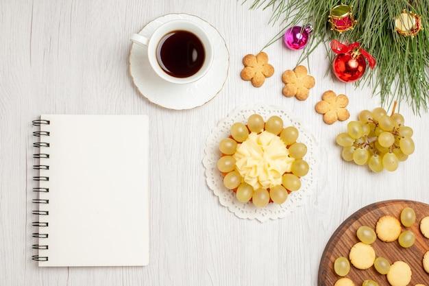 Vista de cima uvas verdes frescas com xícara de chá e bolo na mesa branca.