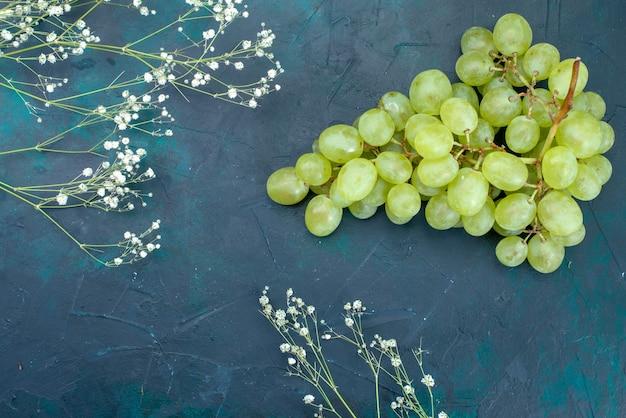Vista de cima uvas verdes frescas na mesa azul fruta fresca e suave cor suculenta