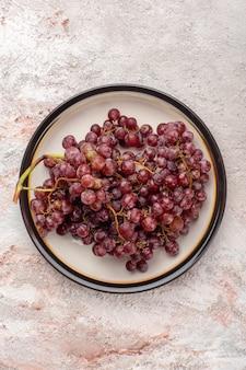 Vista de cima uvas vermelhas frescas, frutas suculentas e maduras dentro do prato na superfície branca