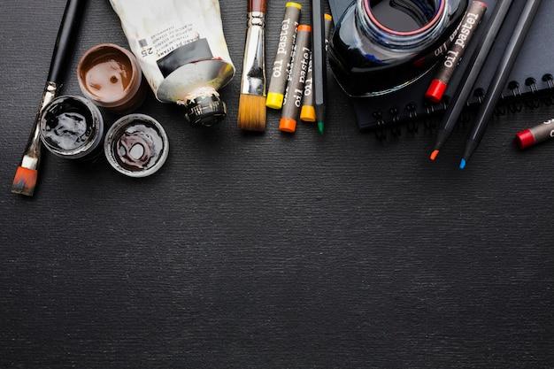 Vista de cima vários pincéis e lápis de cor para copiar o espaço
