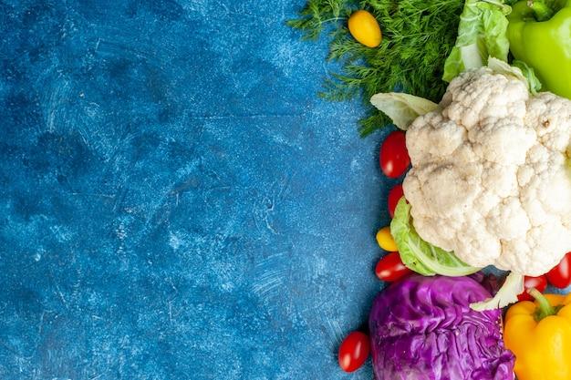 Vista de cima vários vegetais, tomate cereja, cores diferentes, pimentão, couve-flor, repolho vermelho, endro, à direita da mesa azul, copie o local