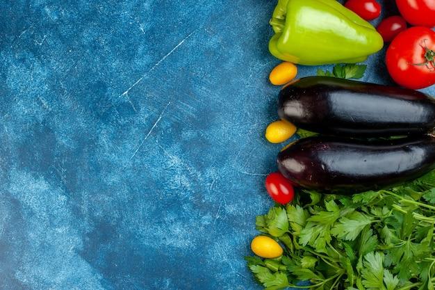 Vista de cima vários vegetais, tomate cereja, pimentão, beringelas, salsa, à direita da mesa azul, copie o local