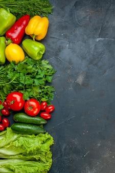Vista de cima vegetais cores diferentes pimentões limão salsa tomates pepinos alface tomate cereja endro na mesa escura com espaço de cópia