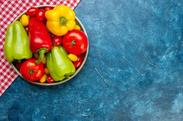 Vista de cima vegetais frescos, tomates cereja, cores diferentes, pimentões, tomates, cumcuat, em, tigela, vermelho e branco, toalha de mesa quadriculada, mesa azul, com, cópia local
