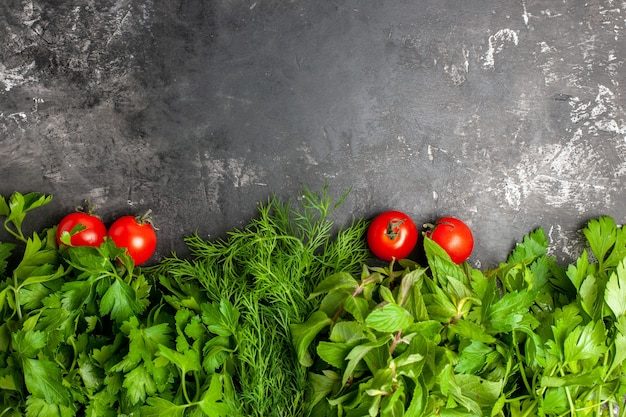 Vista de cima, verdes e tomates em fundo escuro com espaço de cópia