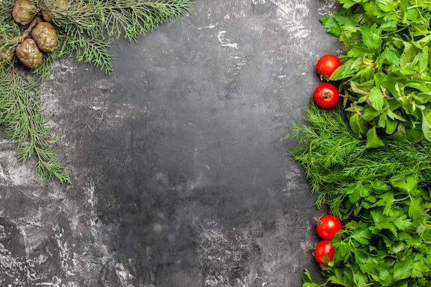 Vista de cima, verdes e tomates na superfície escura