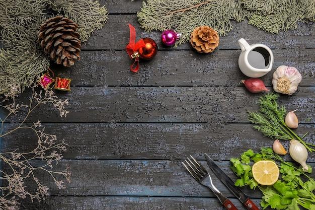 Vista de cima verduras e limão com alho e árvore na mesa escura