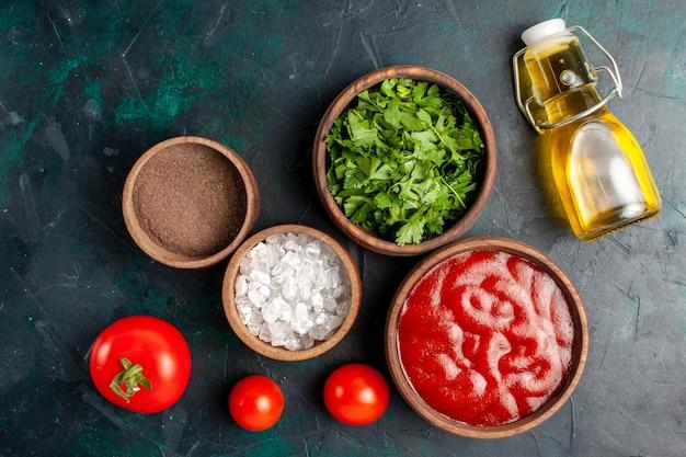 Vista de cima verduras frescas com molho de tomate e azeite de oliva em uma superfície azul-escura ingrediente produto comida refeição