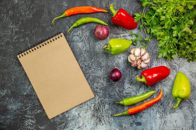 Vista de cima verduras frescas com pimentão e alho na mesa cinza claro