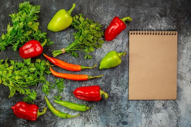 Vista de cima verduras frescas com pimentas na mesa cinza claro