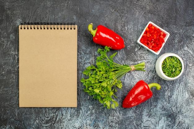 Vista de cima verduras frescas com pimentões vermelhos na mesa cinza claro
