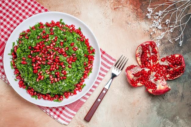 Vista de cima verduras frescas com romãs descascadas em mesa clara com refeição de frutas verdes vermelhas