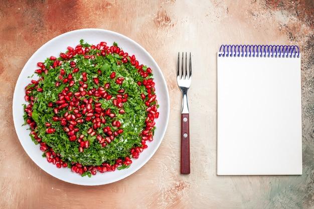 Vista de cima verduras frescas com romãs descascadas na mesa clara refeição cor de frutas verde