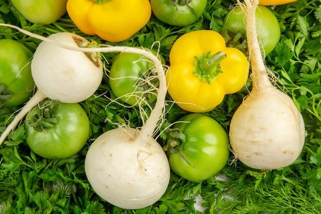 Vista de cima verduras frescas com tomate verde, rabanete e pimentão em fundo branco