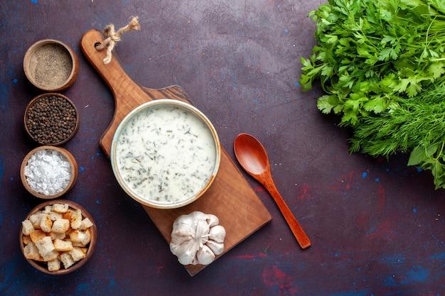 Vista de cima verduras frescas dentro de uma tigela redonda com tostas e temperos dovga na mesa escura, vegetais verdes frescos