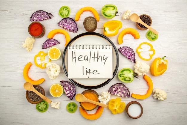 Vista de cima, vida saudável escrita em um caderno em um prato redondo, corte vegetais, especiarias diferentes em pequenas tigelas na superfície branca