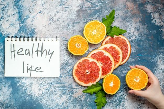 Vista de cima, vida saudável escrita no bloco de notas, corte de laranjas e toranjas, mão feminina segurando tangerina cortada na superfície azul e branca