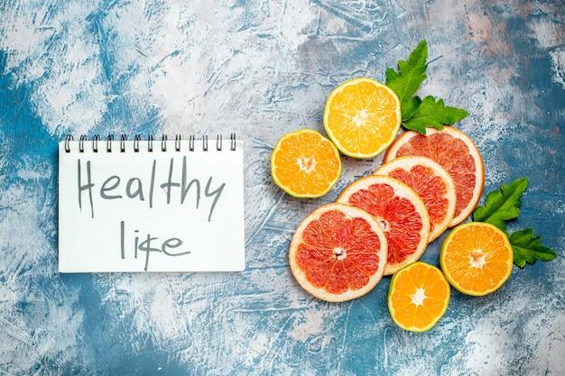 Vista de cima, vida saudável escrita no bloco de notas, corte laranjas e toranjas na superfície azul e branca