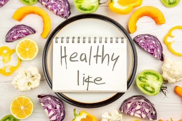 Vista de cima, vida saudável escrita no bloco de notas em uma travessa redonda, corte os vegetais na superfície branca