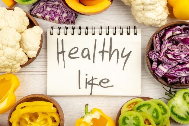 Vista de cima, vida saudável escrita no caderno repolho roxo couve-flor, pimentão amarelo tomate verde em tigelas na superfície de madeira branca