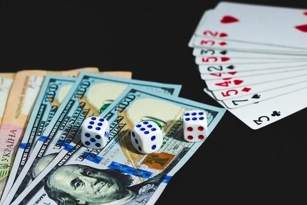Vista de cima. vista de cima. grandes notas de dólares e hryvnia em uma mesa preta. dinheiro, dados e cartas