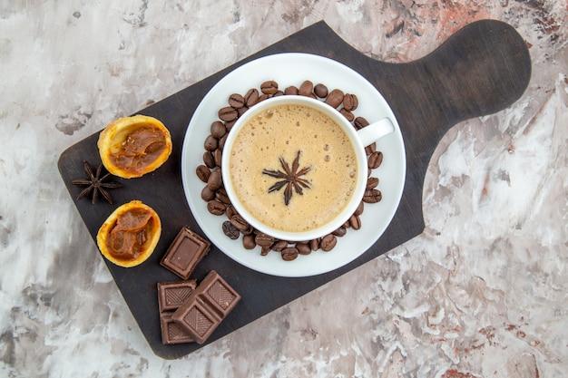 Vista de cima xícara de café com biscoitos de chocolate de anis, grãos de café no pires na placa de madeira na mesa