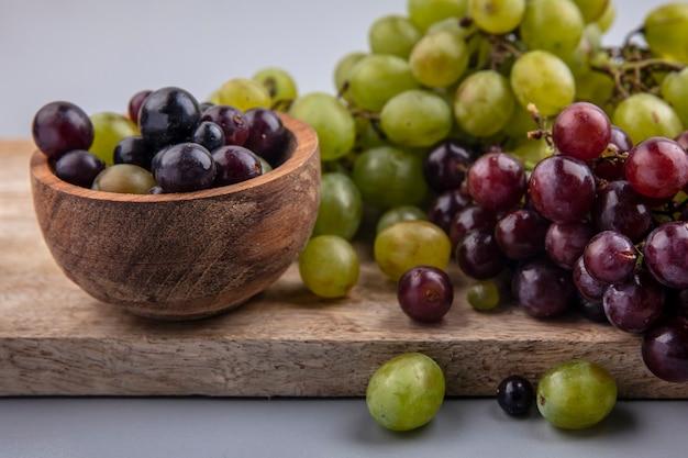 Vista de close-up de bagas de uva em uma tigela e uvas na tábua em fundo cinza