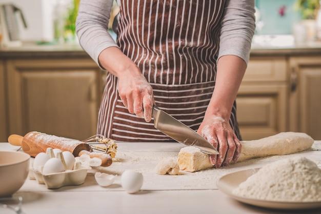 Vista de close-up de duas mãos de mulher corta a massa de faca. uma mulher com um avental listrado cozinhando na cozinha