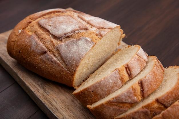 Vista de close-up de pão crocante cortado e fatiado em uma tábua em fundo de madeira