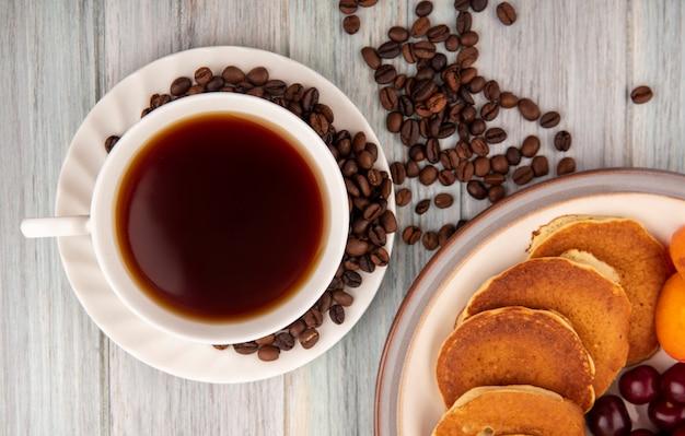 Vista de close-up de uma xícara de chá e grãos de café no pires com prato de panquecas, cerejas, damascos, no fundo de madeira