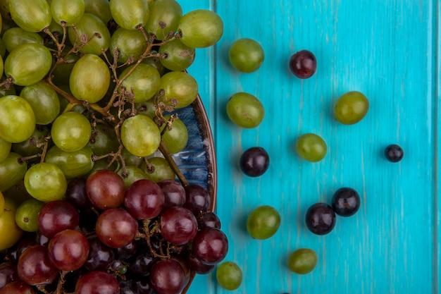 Vista de close-up de uvas em prato e padrão de bagas de grapr em fundo azul