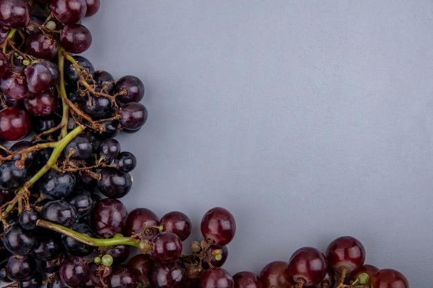 Vista de close-up de uvas pretas e vermelhas em fundo cinza