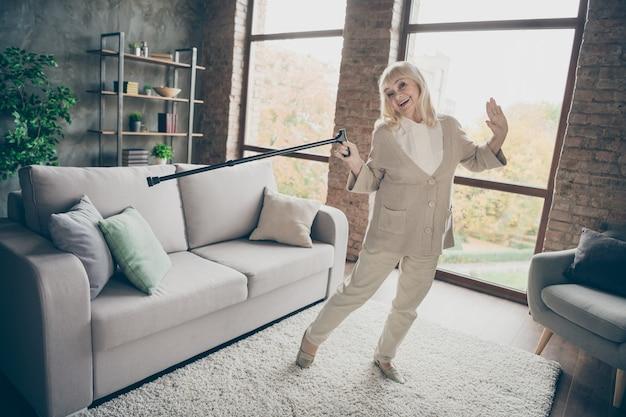 Vista de corpo inteiro de belo atraente saudável alegre alegre vovó de cabelos grisalhos dançando com bengala se divertindo aposentadoria em loft de tijolos industriais casa interior de estilo moderno