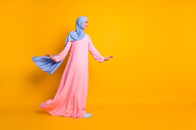 Vista de corpo inteiro de comprimento total de muslimah muito alegre usando vestido hijab olhando de lado andando cópia espaço isolado brilho fundo de cor amarela