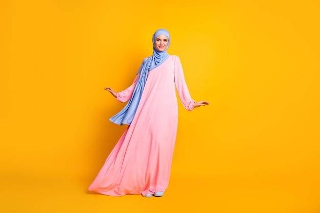 Vista de corpo inteiro de corpo inteiro linda linda alegre muslimah feminina usando vestido hijab posando de fundo amarelo brilhante