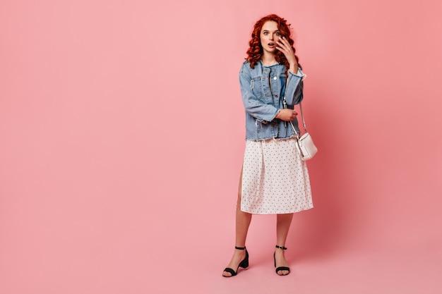 Vista de corpo inteiro de mulher ruiva chocada em sapatos de salto alto. foto de estúdio de menina espantada em pé de jaqueta jeans sobre fundo rosa.
