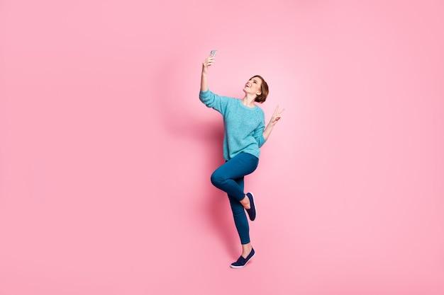 Vista de corpo inteiro dela ela agradável atraente adorável alegre alegre menina de cabelos castanhos se divertindo fazendo selfie mostrando o sinal v