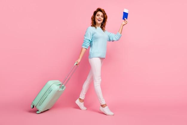 Vista de corpo inteiro dela, ela bonita, atraente, bonita, alegre, de cabelos ondulados, caminhando carregando bagagem, passaporte partindo do exterior isolado sobre fundo rosa pastel